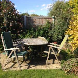 For sale: Hardwood extendible garden table with six recliner chairs with cushions - £150
